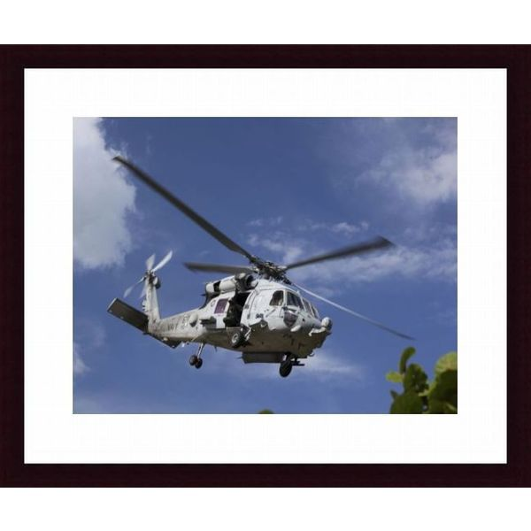 'A Crew Chief looks out the side door of a helicopter in flight' Framed Print