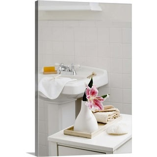 """An orchid flower in a white vase in the bathroom"" Canvas Wall Art"