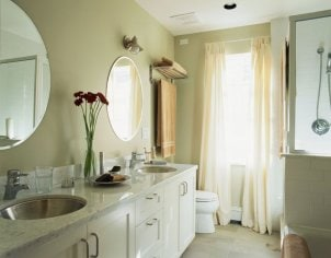 Sheer white curtains provide light in cream-colored bathroom