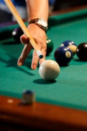 Closeup of pool table and cue stick