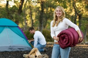 Camping woman holding a sleeping bag