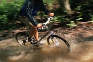 Mountain biker riding through water