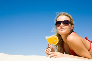 Woman with a drink on the beach