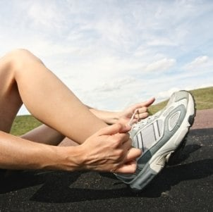 Woman putting on running shoe, sitting on the track