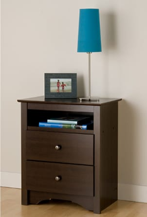 Nightstand with drawers next to a bed