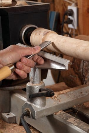 Man carving a table leg on a wood lathe