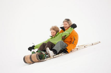 Mother and son sledding together