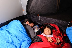 Father and son camping in sleeping bags