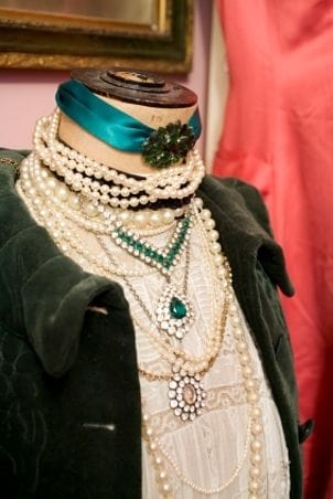 A mannequin dressed in a green velvet jacket and several necklaces and pendants