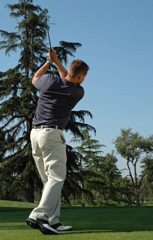 Man taking a swing with a golf iron