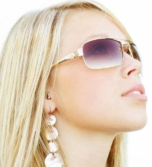 Pretty blonde wearing geometric drop earrings and sunglasses