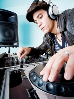 Man wearing headphones and using DJ equipment
