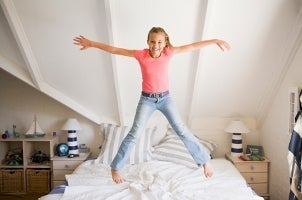 Kid jumping on a bed in her room