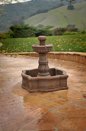 Rustic outdoor fountain complements stone patio