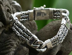Men's fine silver jewelry bracelet sitting on a rock