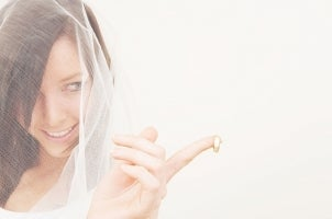 Pretty bride enticingly holds out a gold men's wedding ring
