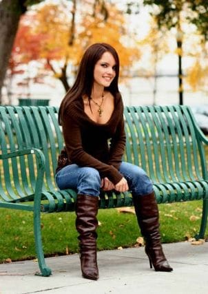 Woman sitting on a bench wearing brown boots