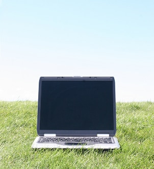 Notebook computer sitting on green grass