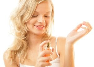 Blonde girl spritzing perfume on her wrist