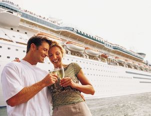 Couple toasting outside their cruise ship