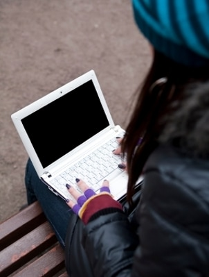Girl on a bench typing on a netbook
