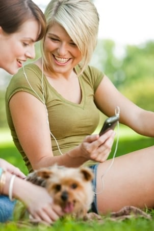 Girls in the park listening to an MP3 player