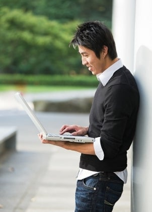Young man standing holding a cheap laptop