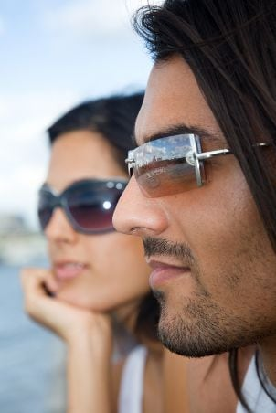 Couple sitting together and wearing sunglasses