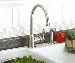 Brushed nickel kitchen faucet against a white tile backsplash