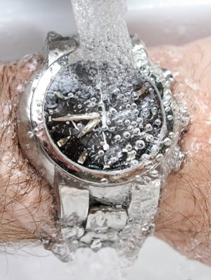 A water-resistant watch under running water
