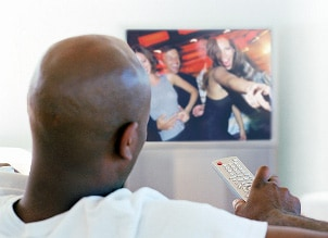 Man holding a remote watching his HD television