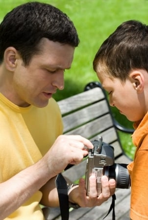 Dad and son inserting a memory card into a camera