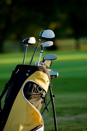 Yellow and black golf bag full of golf clubs on a beautiful golf course