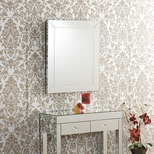 Frameless mirror complements vintage wallpaper and side table