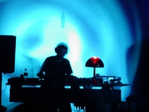 DJ performing with DJ equipment in a club