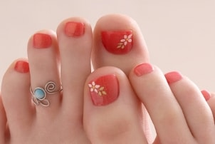 A woman with a bright orange floral pedicure wearing a turquoise and silver toe ring