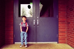 little boy wearing children's school shoes in front of school doors