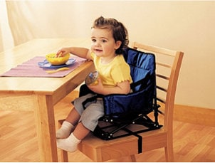 Cute baby girl sitting in a booster seat