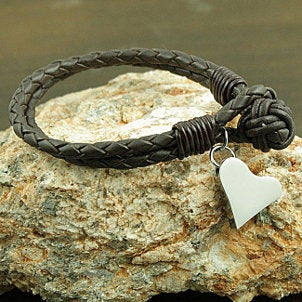 A braided leather bracelet with a silver heart jewelry charm