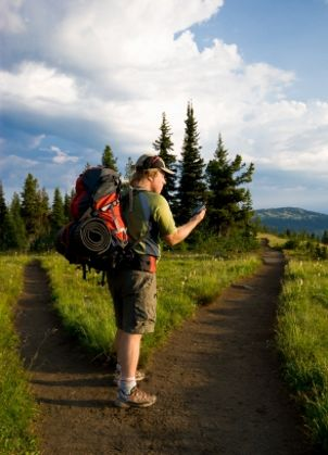Hiker checks GPS at the fork of a trail