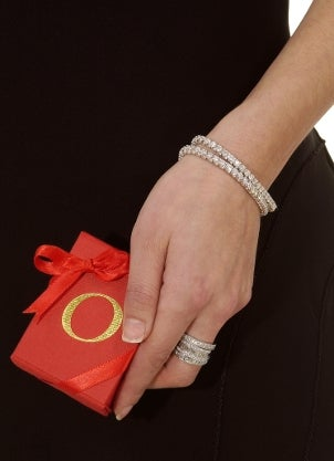 A woman wearing a diamond tennis bracelet and stackable diamond rings