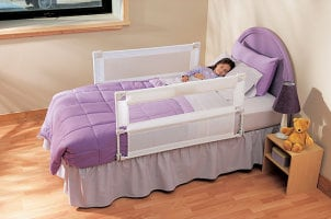 Toddler bed with safety rails and colorful bedding