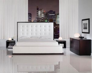 White leather luxury bed with bright city lights in the background