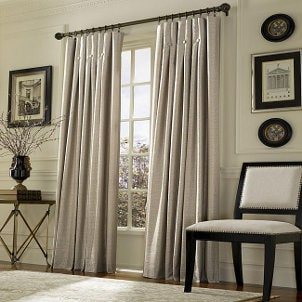 Beige drapes hang from drapery hooks in the living room