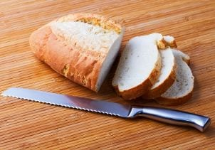 Serrated knife lays next to sliced French bread loaf