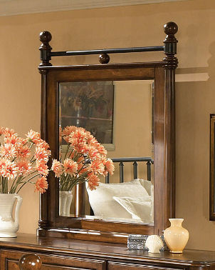 Wooden mirror sits on dresser next to vase of flowers