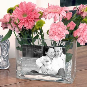 Clear square vase holds family photo and pink flowers