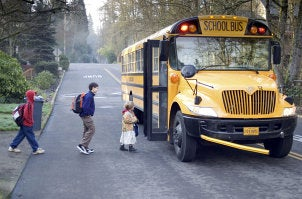 Children crossing the street to board a school bus