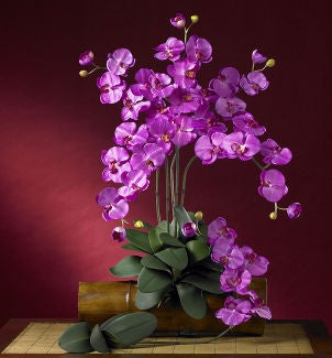 Vibrant silk orchid flower arrangement dresses up table