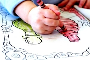 Small kid drawing in a coloring book
